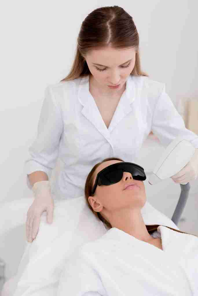young woman getting laser hair removal procedure on face in salon